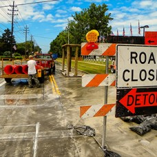 Construction site with sign in the foreground that reads 'Road Closed Detour'